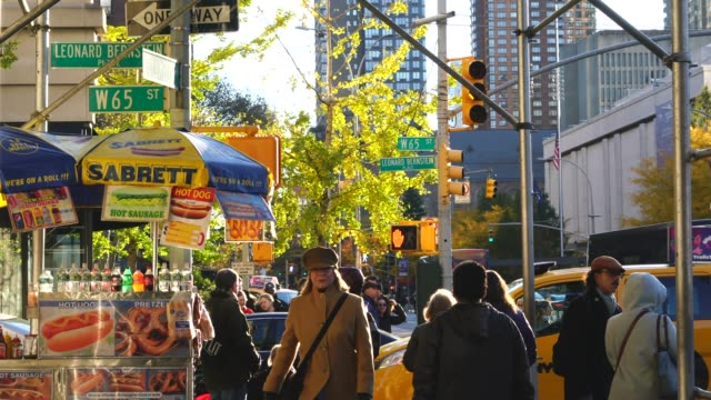 people walk on the sidewalk beside the hot dog stand at upper west manhattan at new york ny usa on nov. 17 2018. - ginkgo stock videos & royalty-free footage