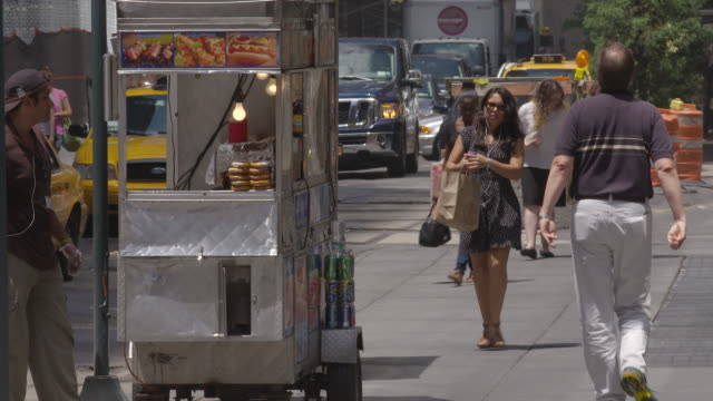 people walk on the sidewalk passing a hot dog vendor cleaning his cart on a sunny summer day. - concession stand stock videos and b-roll footage