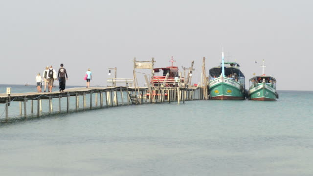 People walk on wooden jetty with excursion ships