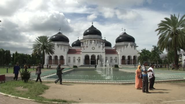 people walk outside mesjid raya baiturrahman mosque prior to the ten year anniversary of the 2004 earthquake and tsunami in banda aceh indonesia - religiöse stätte stock-videos und b-roll-filmmaterial