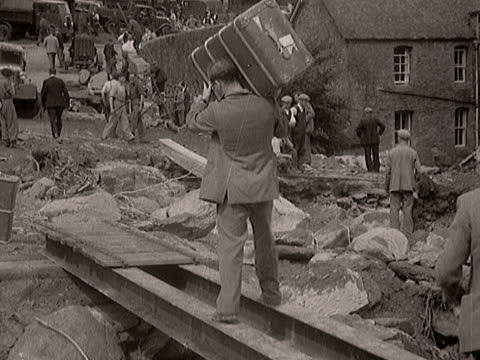 people walk over a makeshift bridge in the village of lynmouth following the flooding disaster. - devon stock videos & royalty-free footage