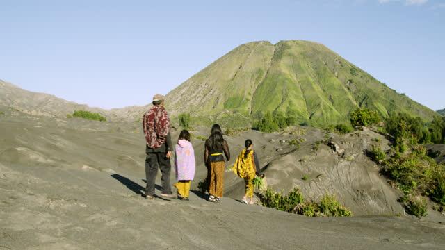 people walk over sand dune toward mount batok, java. - unschuld stock-videos und b-roll-filmmaterial