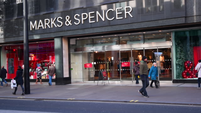 people walk past a branch of marks and spencer in oxford street on november 7, 2016 in london, england. british high street retailer marks and... - finance and economy stock videos & royalty-free footage