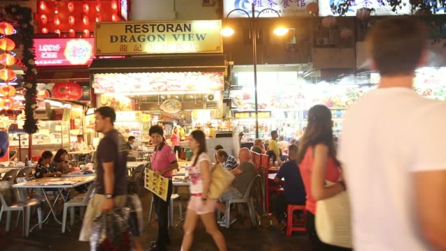 people walk past a food stall at the jalan alor food street in kuala lumpur, malaysia, on monday, july 21 people sit at outdoor restaurants at the... - kuala lumpur stock videos & royalty-free footage