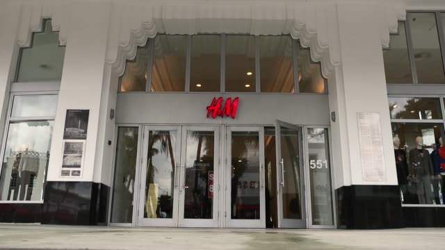 People walk past a HM clothing store on January 9 2018 in Miami Beach Florida HM apologized on Monday after the Swedish clothing retailer's website...