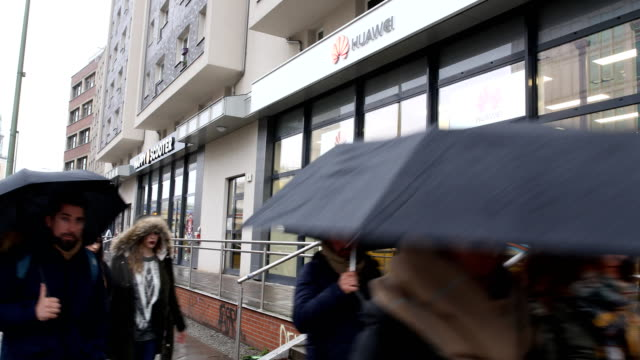 people walk past a huawei customer service center on on march 15, 2019 in berlin, germany. the u.s. government has warned germany not to consider... - big brother orwellian concept stock videos & royalty-free footage