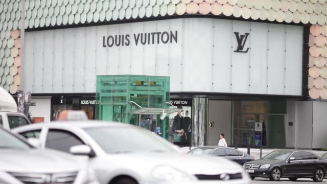 people walk past a louis vuitton store, operated by lvmh moet hennessy louis vuitton sa, at lotte avenuel, lotte shopping co.'s luxury brand... - salvatore ferragamo stock videos & royalty-free footage