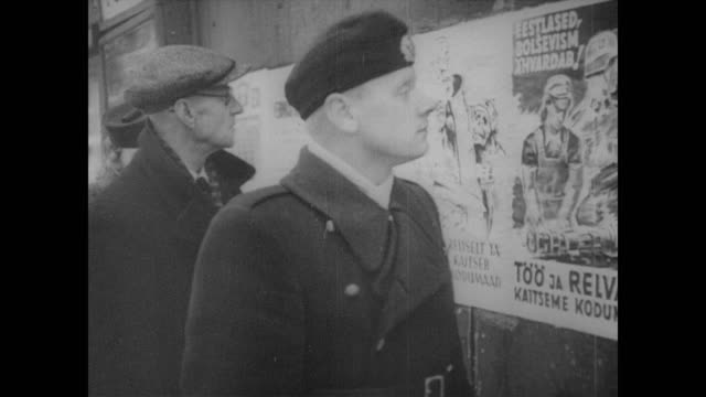 People walk past a poster stating Coldblooded and courageously protect Estonian home country