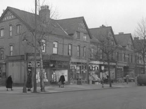 vidéos et rushes de people walk past a row of local shops in manchester - 1950 1959
