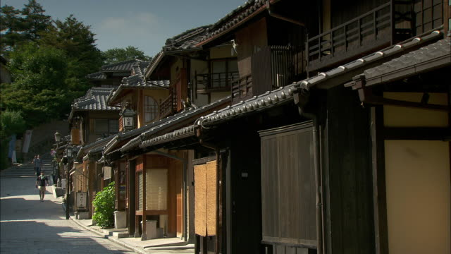 People walk past a row of traditionally designed buildings in Kyoto.