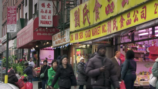 people walk past a sea food market in chinatown nyc. - chinatown stock videos & royalty-free footage