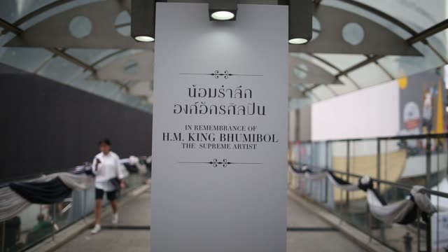 people walk past a shrine to the late thai king bhumibol adulyadej outside emquartier shopping mall in bangkok thailand on saturday oct 21... - king of thailand stock videos and b-roll footage