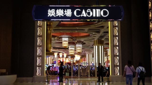 People walk past an entrance to a casino at the City of Dreams casino resort developed by Melco Crown Entertainment Ltd in Macau China on Thursday...