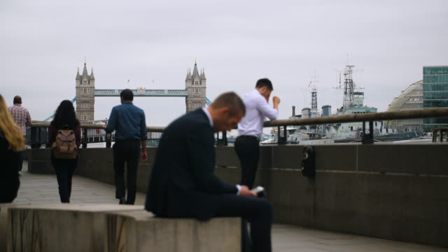 people walk past, and relax by, the river thames with views of tower bridge in the background - employment issues stock videos & royalty-free footage