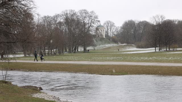people walk past eisbach river at english garden park while it snows at first spring weekend during the coronavirus pandemic on march 20, 2021 in... - ミュンヘン エングリッシャーガルテン点の映像素材/bロール