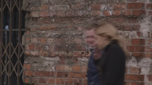 people walk past holes in the wall of a former ghetto, warsaw - moving past stock videos & royalty-free footage