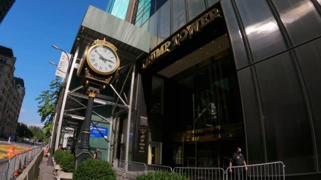 stockvideo's en b-roll-footage met people walk past metal barriers in front of the 5th avenue entrance of trump tower on september 28, 2020 in new york city. - redactioneel