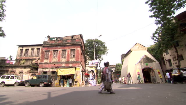 People walk past run-down buildings in Kolkata. Available in HD.