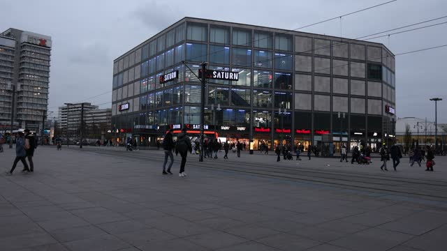 people walk past saturn, a popular home electronics store, advertising pre-christmas sales at alexanderplatz on cyber monday during the second wave... - electronics store stock videos & royalty-free footage