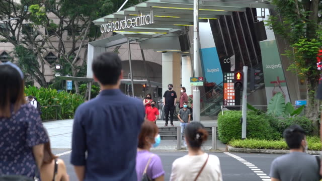 vídeos y material grabado en eventos de stock de people walk past the apple store on orchard road people line up outside a robinsons department store on orchard road in singapore people walk outside... - escritura occidental