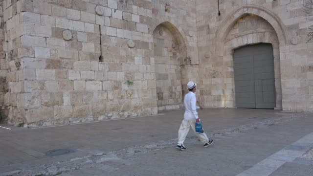 people walk past the closed doors of jaffa gate in the old city hours after movement restrictions imposed due to spike of coronavirus pandemic on... - jaffa stock videos & royalty-free footage