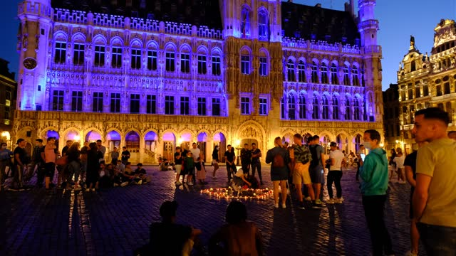 vidéos et rushes de people walk past the grand place on june 13, 2021 in brussels, belgium. several local landmarks will be illuminated in nato colours to mark the nato... - grand lit