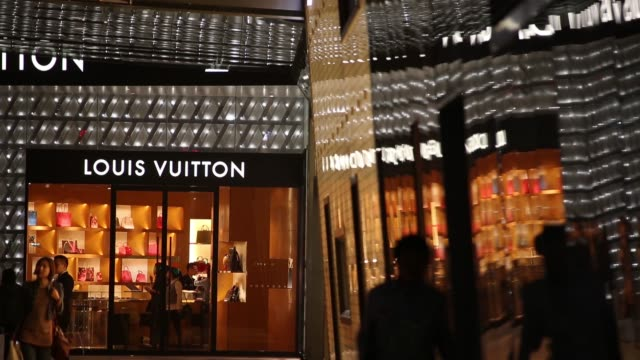 people walk past the illuminated exterior of a louis vuitton store, operated by lvmh moet hennessy louis vuitton sa, at night in the lujiazui... - lujiazui stock videos & royalty-free footage