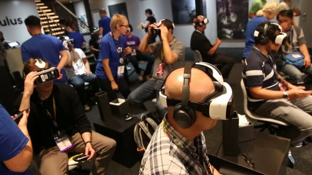 people walk past the oculus rift virtual reality headset booth during the e3 electronic entertainment expo in los angeles, california, u.s., on... - television game show video stock e b–roll
