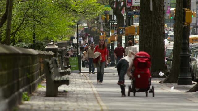 people walk right outside the park on the sidewalk of central park west and 67th street. - ベンチ点の映像素材/bロール