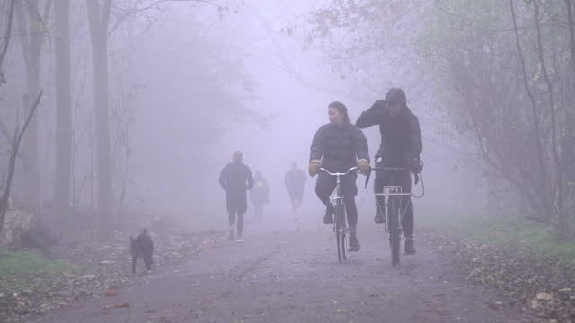 people walk, run and cycle through hackney marshes as thick fog descends on the country on november 27, 2020 in london, england. the unique weather... - atmospheric mood stock videos & royalty-free footage
