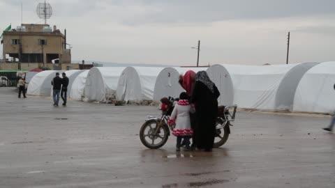 people walk through a bab al-salam syrian refugee camp near in azaz syria on the border with turkey. - イスラエルパレスチナ問題点の映像素材/bロール