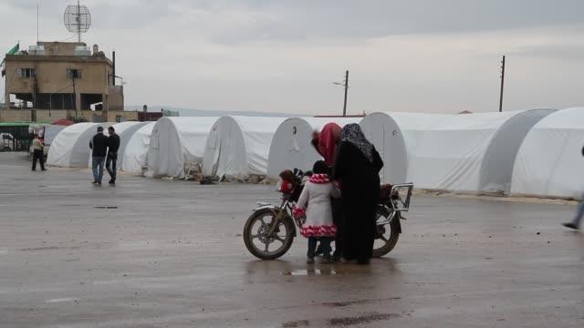 People walk through a Bab alSalam Syrian refugee camp near in Azaz Syria on the border with Turkey