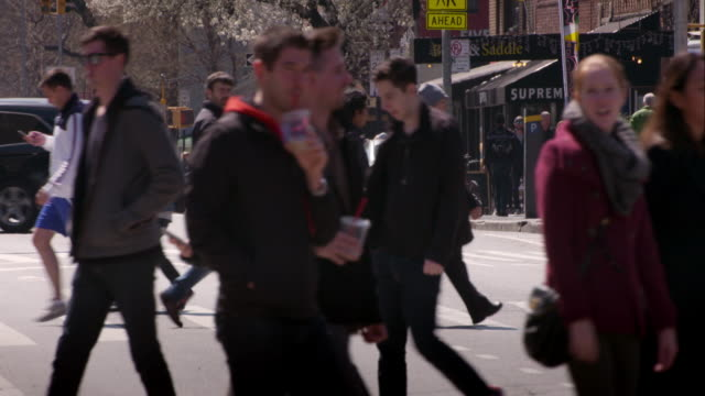 People walk through a busy intersection in Greenwich Village on 7th Avenue in Manhattan.