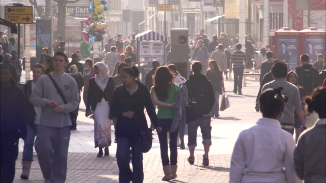People walk through a pedestrianised area of Bristol. Available in HD.