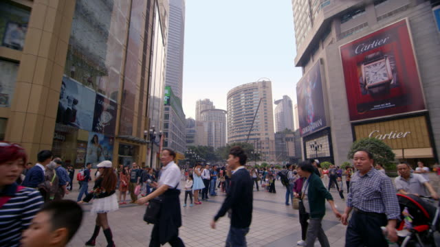 People walk through a shopping district in the city of Chongqing.