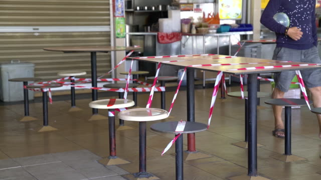 people walk through an empty food center in the kallang area on day 15 of the covid19 circuit breaker meant to slow the spread of the coronavirus in... - ordering stock videos & royalty-free footage