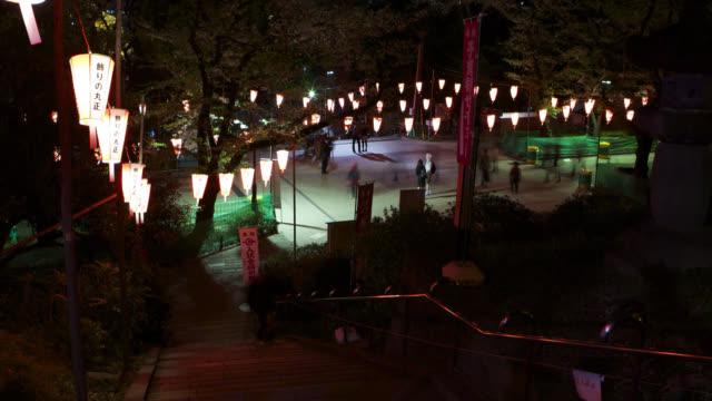 People walk through cherry blossom festival at night, Tokyo, Japan.