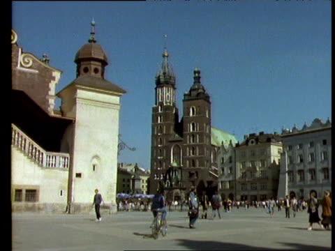 people walk through city square, krakow, poland - poland stock videos & royalty-free footage