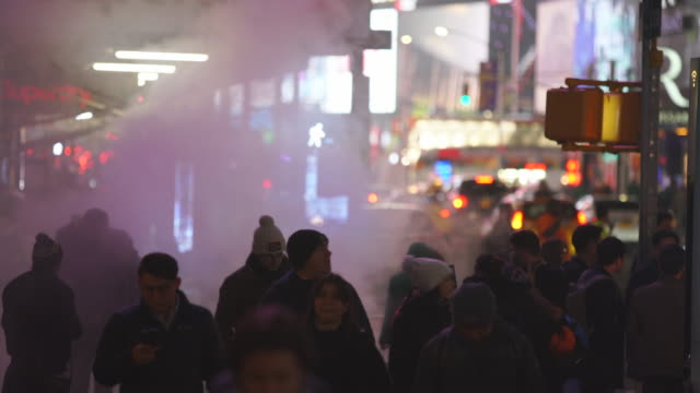 people walk through on the sidewalk among the rising steam in the night around the times square in midtown manhattan new york city ny usa on jan. 14 2020. - yellow taxi stock videos & royalty-free footage