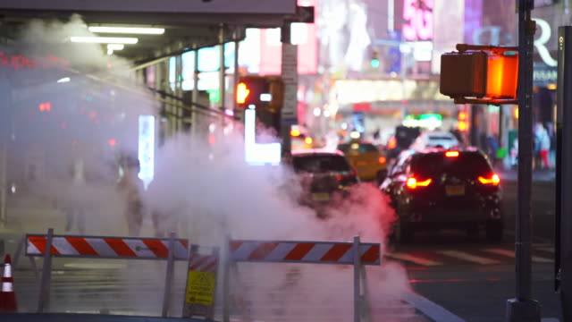 people walk through on the sidewalk among the rising steam in the night around the times square in midtown manhattan new york city ny usa on jan. 14 2020. - nordamerika stock-videos und b-roll-filmmaterial