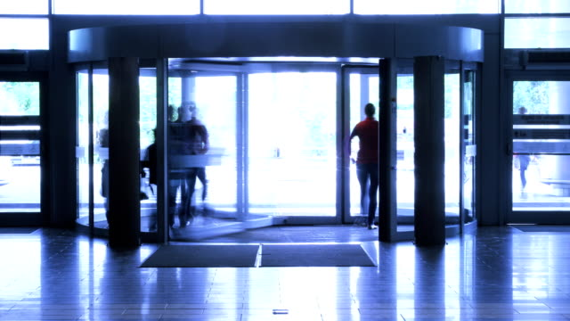 People walk through revolving door