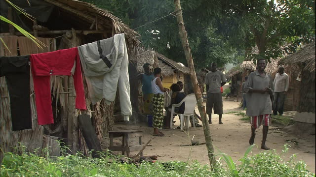 people walk through rural village, clothes on line in foreground, niger delta, kura region, nigeria - washing line stock videos & royalty-free footage