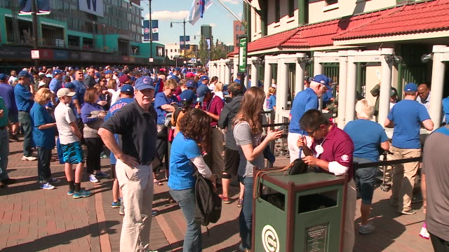 people walk through security line outside wrigley field before cubs playoffs game on oct. 9, 2017. - playoffs stock videos & royalty-free footage