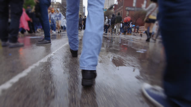 People walk through the crowded streets of Austin in the rain during South By Southwest