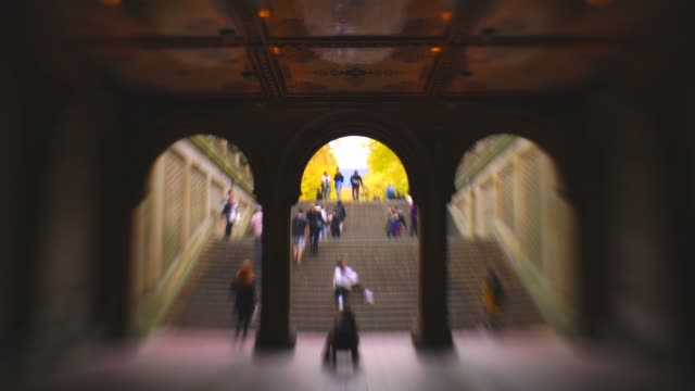 vídeos y material grabado en eventos de stock de people walk through the under pathway of bethesda terrace to go to the mall surrounded by autumn color trees at central park new york ny usa on nov. 01 2018. - fuente bethesda
