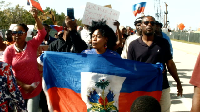people walk together as the maralago resort where president donald trump spent the last few days is seen in the background as they condemn president... - flag haiti stock videos & royalty-free footage