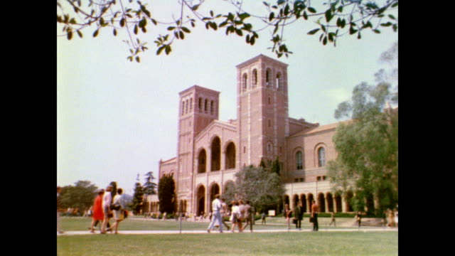 vidéos et rushes de / people walking about the grounds of ucla campus / students relaxing and visiting on the grounds / students sit on wall next to sign that reads... - professor