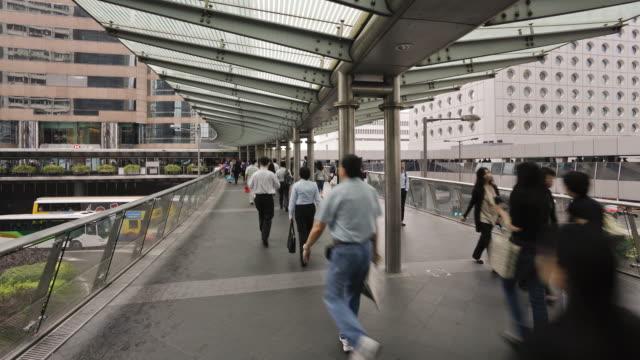 people walking across an elevated walkway in central, hong kong island, hong kong, china, time-lapse - hong kong island stock videos & royalty-free footage