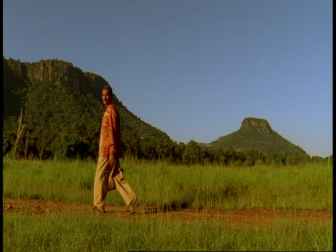 wa people walking across path, mountains in background, bandhavgarh national park, india - bandhavgarh national park stock videos and b-roll footage