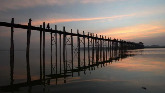 vídeos y material grabado en eventos de stock de ms people walking across wooden u bein bridge at sunset / mandalay, mandalay region, myanmar - myanmar